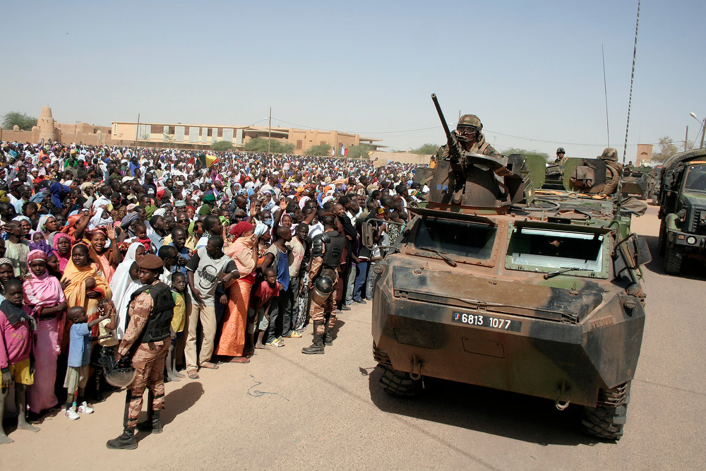 Description of . A French  armored personal carrier drives past thousands who gathered to greet French President Francois Hollande  on his visit to Timbuktu, Mali, Saturday Feb. 2, 2013, making a triumphant stop six days after French forces parachuted into Timbuktu to liberate the fabled city from the radical Islamists occupying it. (AP Photo/Harouna Traore)