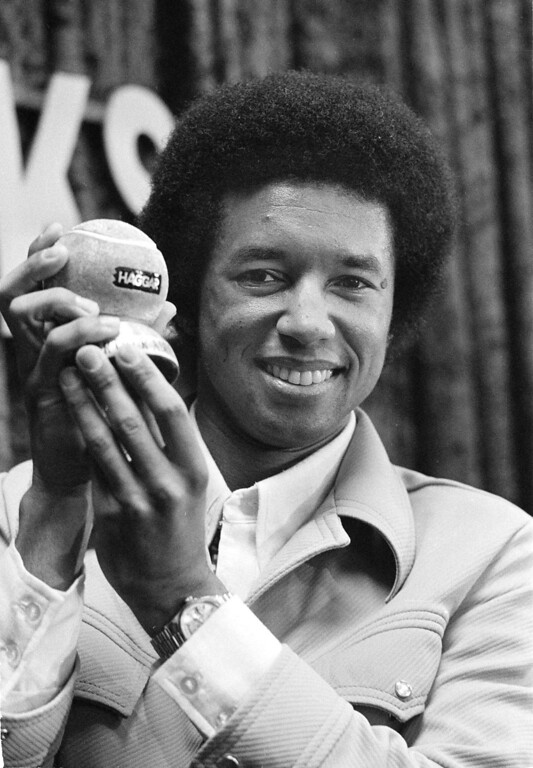 . U.S. Tennis star Arthur Ashe holds a 24-karat, solid gold tennis ball that was presented to him in Dallas, May 5, 1975 as winner of the Haggar Slacks Scoreboard competition. The ball weighs about 13 pounds and is valued at $33,333.33. Ashe will be trying to win the World Championship of Tennsi that gets underway this week in Dallas. (AP Photo/Ferd Kaufman)