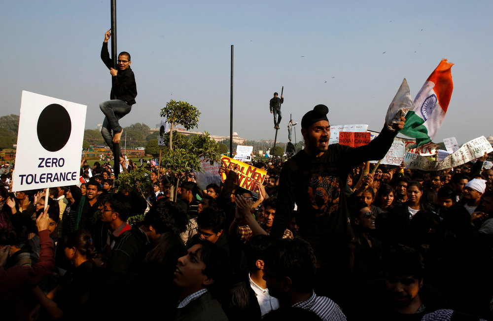 Description of . Indian protesters climb flag posts and shout slogans during a protest in New Delhi, India, Saturday, Dec. 22, 2012. Police in India's capital used tear gas and water cannons Saturday to push back thousands of people who tried to march to the presidential mansion to protest the recent gang rape and brutal beating of a 23-year-old student on a moving bus. (AP Photo/Tsering Topgyal)