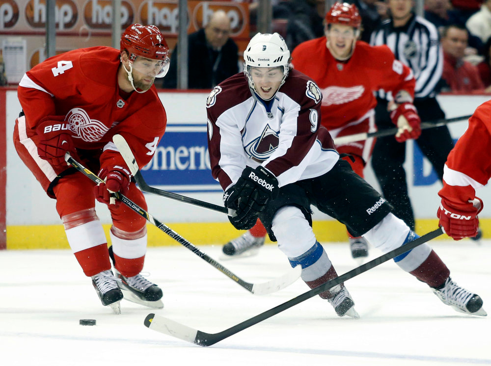 . Detroit Red Wings defenseman Jakub Kindl (4) tries to take the puck from Colorado Avalanche center Matt Duchene (9) in the first period of an NHL hockey game Monday, April 1, 2013, in Detroit. (AP Photo/Duane Burleson)