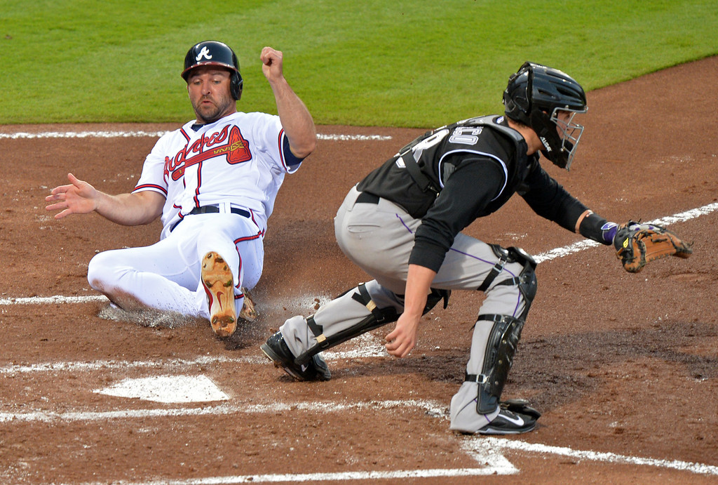 . Atlanta Braves\' Dan Uggla slides into home behind Colorado Rockies catcher Jordan Pacheco during the second inning of a baseball game Friday, May 23, 2014, in Atlanta. (AP Photo/Atlanta Journal Constitution, Brant Sanderlin) GWINNETT OUT  MARIETTA OUT   LOCAL TV OUT (WXIA, WGCL, FOX 5)