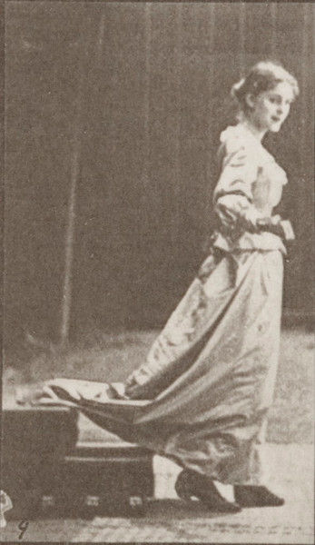 Woman descending stairs, looking around and waving a fan