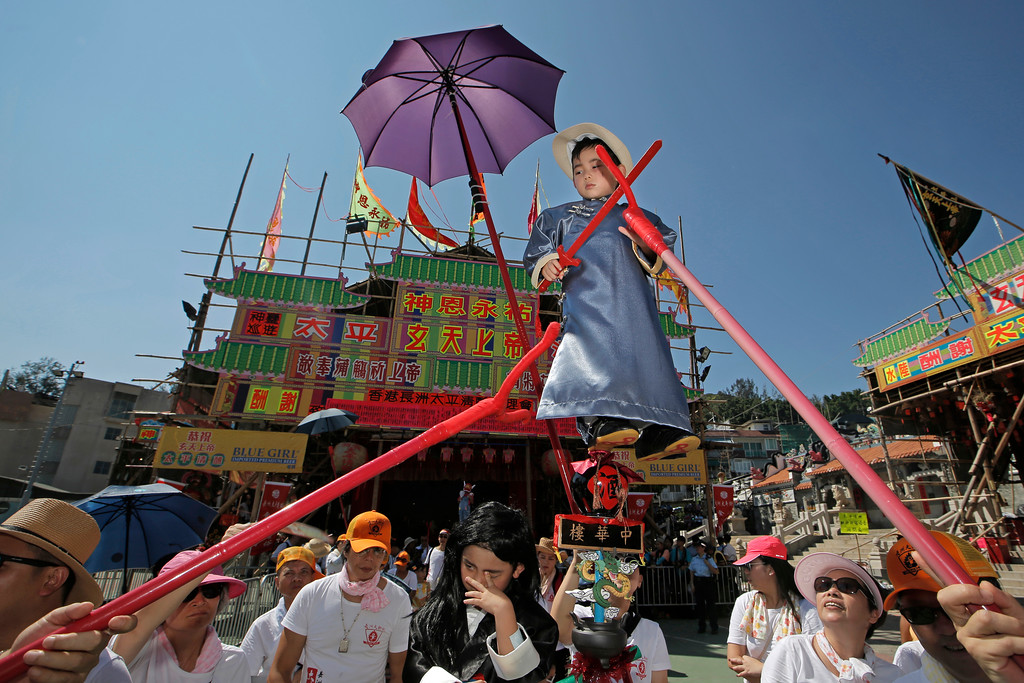 . A child dressed in a traditional Chinese costume floats in the air, supported by a rig of hidden metal rods, during a parade on the outlying Cheung Chau island in Hong Kong to celebrate the Bun Festival Tuesday, May 22, 2018. Bun Festival, the Taoist God of the Sea, is worshipped and evil spirits are scare away by loud gongs and drums during the procession. The celebration includes bun scrambling, parades, opera performances, and children dressed in colorful costumes. (AP Photo/Kin Cheung)