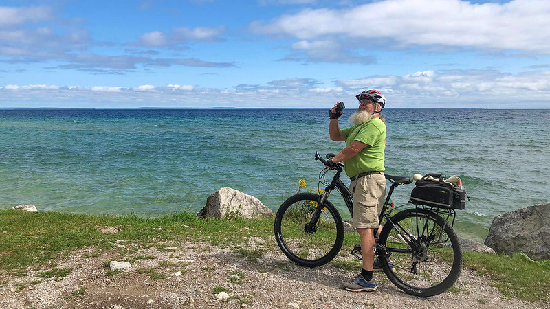 John standing over Trek Sky taking photo Lake Huron