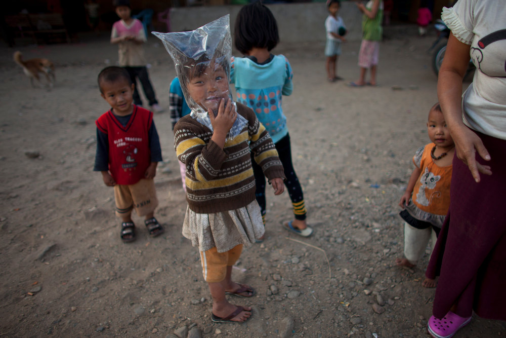 . A girl puts a plastic bag on her head while she plays at an Internally Displaced Persons refuge camp set up at a land of Woichyai Baptist Church in the town of Laiza, in northern Myanmar\'s Kachin-controled region, Tuesday, Jan. 29, 2013. (AP Photo/Alexander F. Yuan)