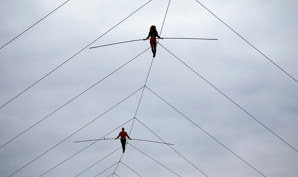 . Nik Wallenda and his sister Lijana Wallenda perform on a tightrope before the NASCAR Sprint Cup Series auto race at Charlotte Motor Speedway in Concord, N.C., Saturday, Oct. 12, 2013. (AP Photo/Terry Renna)