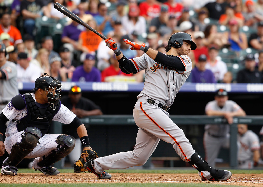 . San Francisco Giants\' Brandon Crawford, right, swings at a pitch as Colorado Rockies catcher Yorvit Torrealba fields the throw in the fifth inning of a baseball game in Denver on Saturday, June 29, 2013. (AP Photo/David Zalubowski)