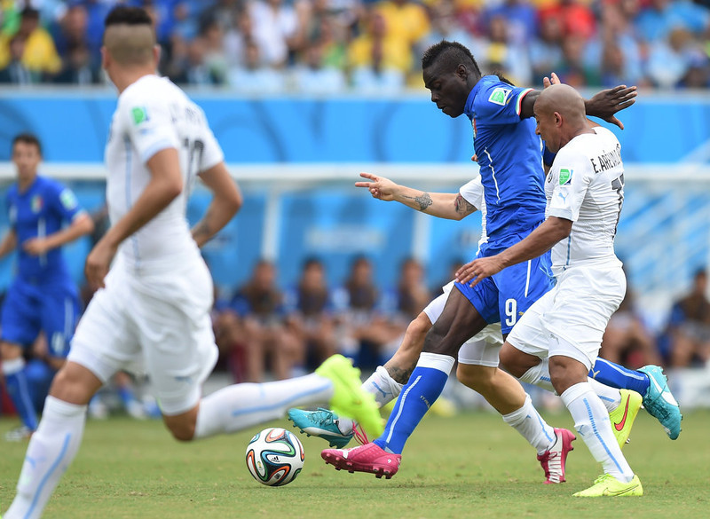 . Italy\'s forward Mario Balotelli (L) vies with Uruguay\'s midfielder Egidio Arevalo Rios during a Group D football match between Italy and Uruguay at the Dunas Arena in Natal during the 2014 FIFA World Cup on June 24, 2014.   JAVIER SORIANO/AFP/Getty Images