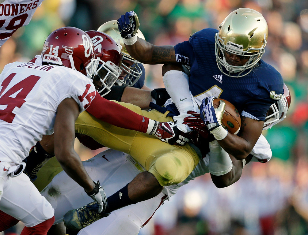 . Notre Dame\'s George Atkinson III (4) is tackled by Oklahoma\'s Geneo Grissom, behind, during the second half of an NCAA college football game on Saturday, Sept. 28, 2013, in South Bend, Ind. Oklahoma defeated Notre Dame 35-21. (AP Photo/Darron Cummings)