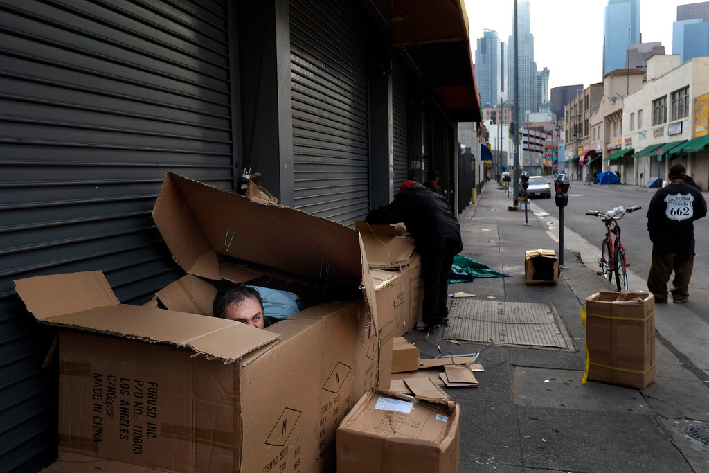 . Antonio Garcia, 54, left, who introduced himself as a mathematician, peeks through the opening of his makeshift shelter made of cardboard boxes in the Skid Row area of Los Angeles, Friday, March 29, 2013. (AP Photo/Jae C. Hong)