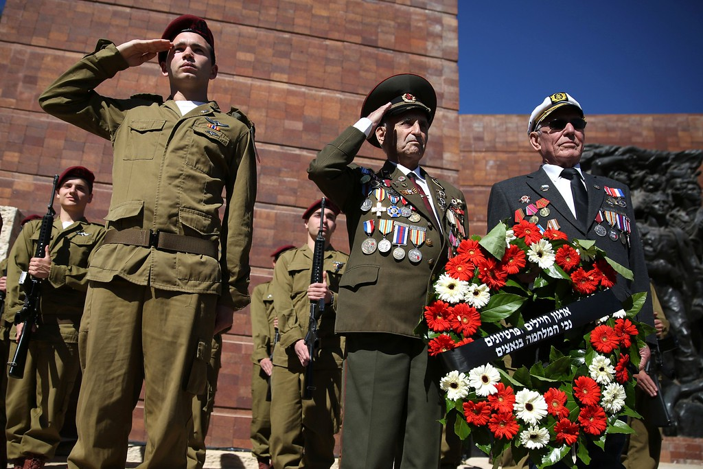 . World War II veterans hold a wreath as they stand next to an honor guard of Israeli soldiers during the annual Holocaust Remembrance Day ceremony at the Yad Vashem Holocaust Memorial in Jerusalem, on May 5, 2016. The state of Israel marks the annual Memorial Day commemorating the six million Jews murdered by the Nazis in the Holocaust during World War II. / AFP PHOTO / GALI TIBBON/AFP/Getty Images