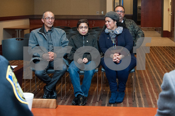 12/19/17 Wesley Bunnell | Staff 12 year old Armani Dante Rivera received recognition before the Police Commissioners meeting on Tuesday evening for his assistance to the New Britain Police Department. Dante's father Arquipo Rivera, L, Armani Dante Rivera and his mother Victoria Rivera.