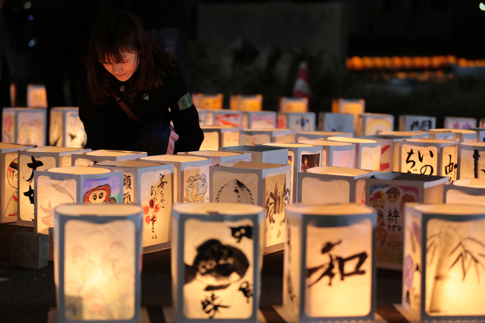 . A volunteer looks at paper lanterns during a memorial held in remembrance of victims of the March 11, 2011 earthquake and tsunami at Yuriage Junior High School on March 11, 2014 in Natori, Miyagi prefecture, Japan. On March 11 Japan commemorates the third anniversary of the magnitude 9.0 earthquake and tsunami that claimed more than 18,000 lives, and subsequent nuclear disaster at the Fukushima Daiichi Nuclear Power Plant.  (Photo by Yuriko Nakao/Getty Images)