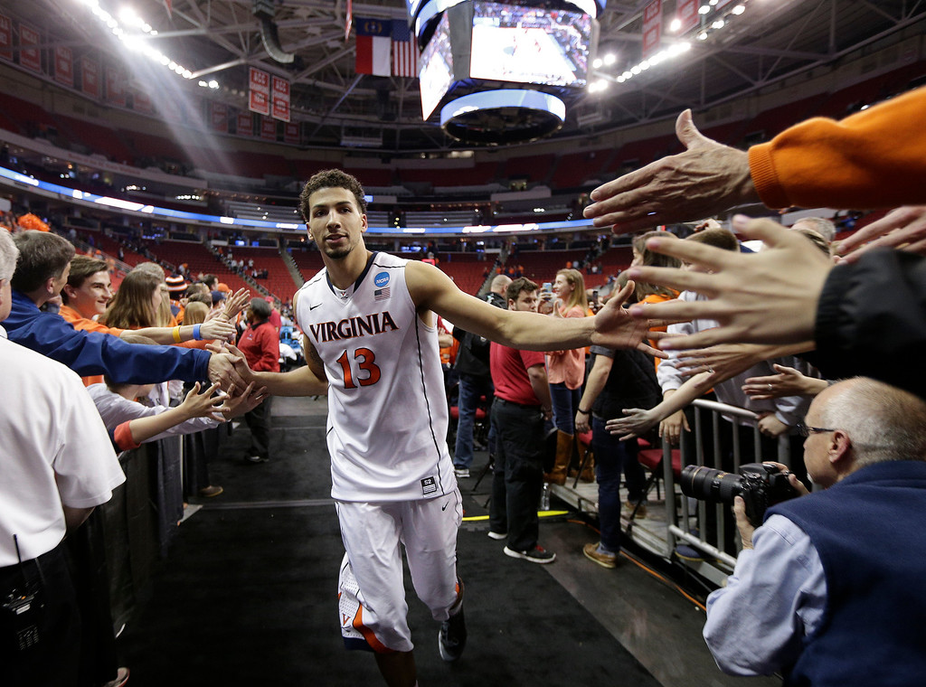 . Virginia forward Anthony Gill (13) slaps the hands of fans after the second half of an NCAA college basketball third-round tournament game against Memphis, Sunday, March 23, 2014, in Raleigh, N.C. Virginia won 78-60. (AP Photo/Chuck Burton)