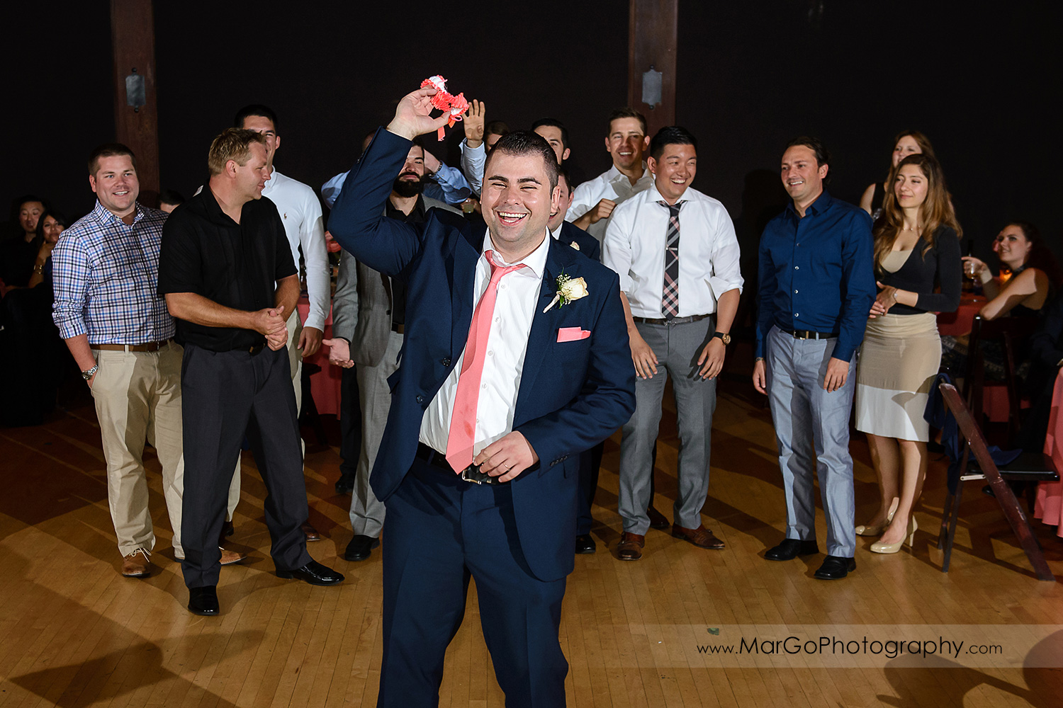 groom tossing garter during wedding reception at Saratoga Foothill Club