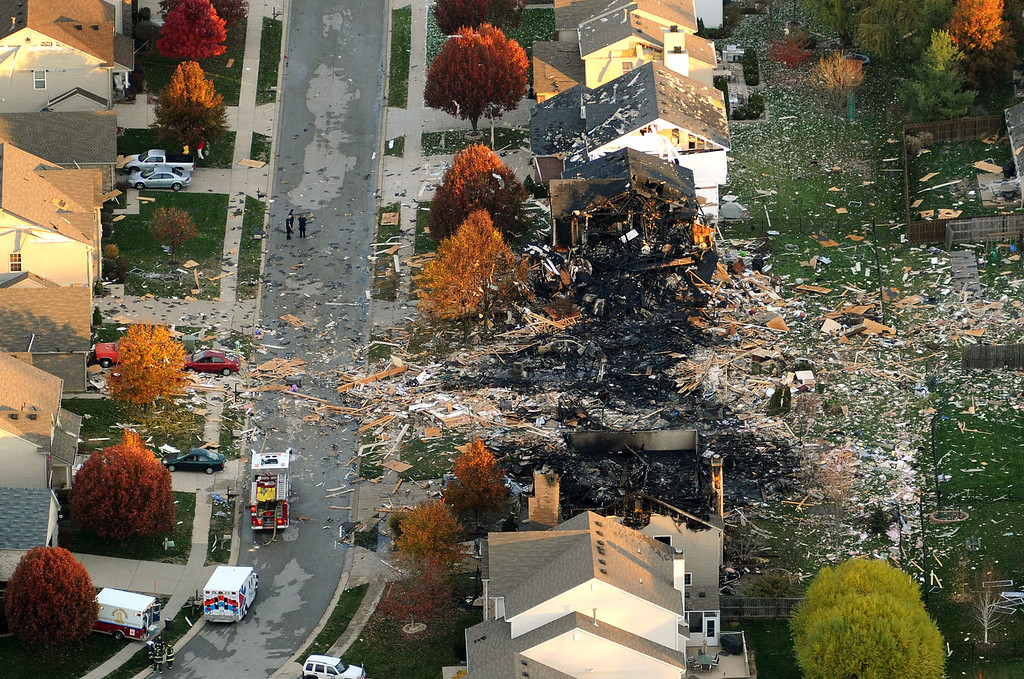. In this Nov. 11, 2012 file aerial photo, the two homes that were leveled and the numerous neighboring homes that were damaged from a massive explosion that sparked a huge fire and killed two people are shown in Indianapolis.  Nearly three dozen homes were damaged or destroyed, and seven people were taken to a hospital with injuries. The powerful nighttime blast shattered windows, crumpled walls and could be felt at least three miles away. Authorities have said they believe the explosion was intentional and caused by natural gas but have released no other details.  (AP Photo/The Indianapolis Star, Matt Kryger, File)  NO SALES