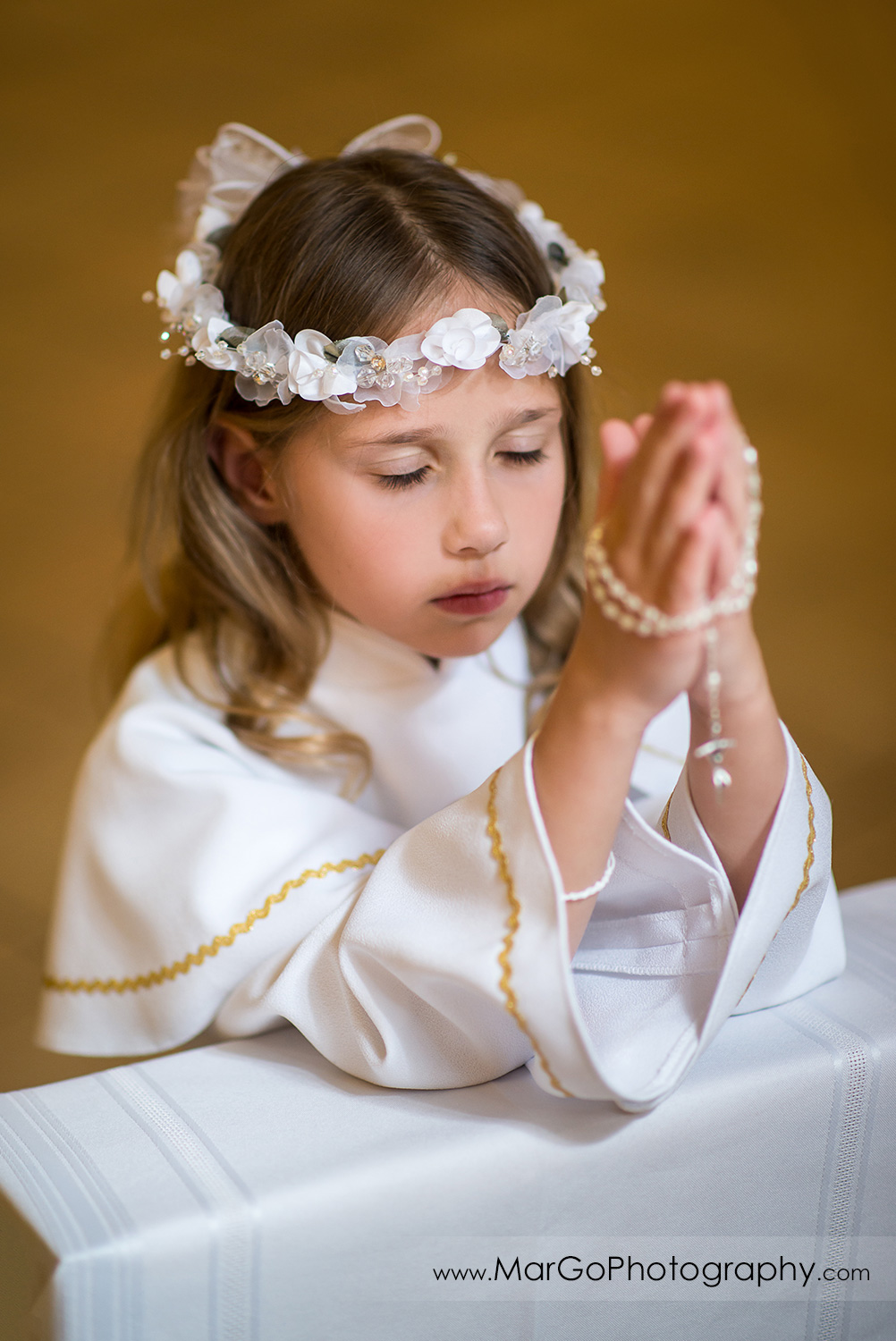 first communion girl in white alb holding rosary in folded hands in wooden San Jose church pews - focus on face