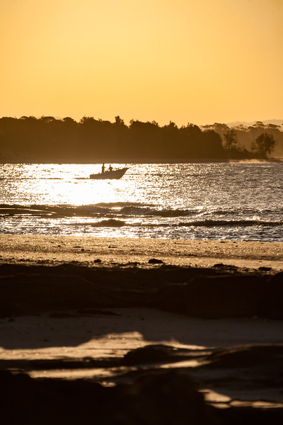 A boat is silhouetted heading out to see as the sunsets - Unnamed Road, Woody Head, New South Wales, Australia (AU)