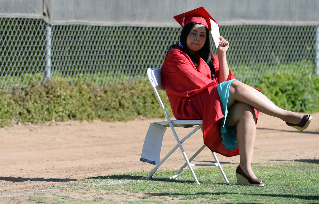 . A student shields her face from the sun prior to the Whittier High School graduation at Whittier College in Whittier, Calif., on Wednesday, June 4, 2014.  (Keith Birmingham/Pasadena Star-News)