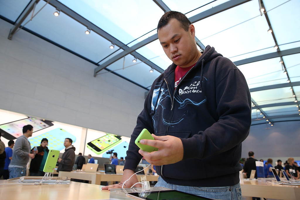 . An Apple Store customer looks at the new Apple iPhone 5C at an Apple Store on September 20, 2013 in Palo Alto, California.   (Photo by Justin Sullivan/Getty Images)