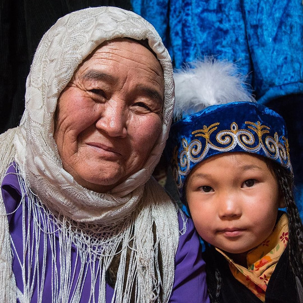 "Yurt encounter, Kyrgyzstan — spanning the generations. Grandmother and grandchild from the Chuy region of Kyrgyzstan. Show curiosity and you will be rewarded. This holds true in most of our travels, but especially in Kyrgyzstan where people are often just as curious about you as you are about them. Ask a question and next thing you know, you're hanging out in a yurt with a grandma, the local elders, and their grandchildren. We experienced this in our interactions with Kyrgyz visitors of the World Nomad Games, as well as the participants. People were having fun, living life, and they wanted to share. To say of Kyrgyz culture that it's ""welcoming"" is sort of an understatement. Kyrgyz people might not even refer to themselves as welcoming, rather ""This is just who we are."" More on our interactions at the World Nomad Games in the latest post on our blog (link in profile). via Instagram http://ift.tt/2cVreEB"