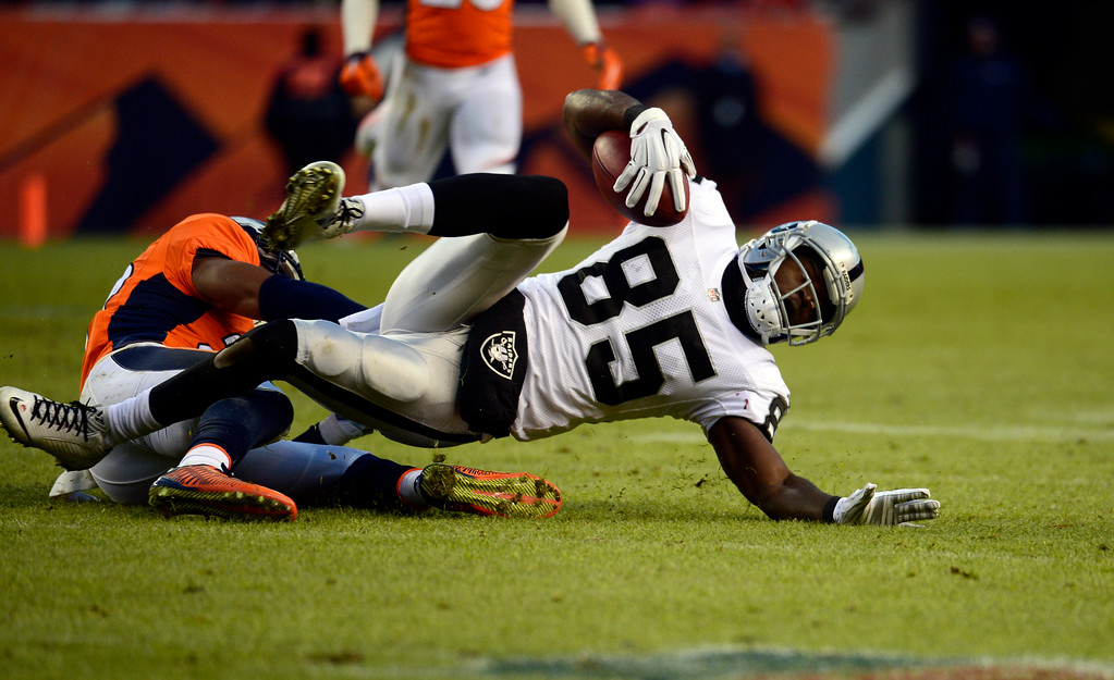 . DENVER, CO - DECEMBER 28: Kenbrell Thompkins (85) of the Oakland Raiders pulls in a catch for a first down during the third quarter.  The Denver Broncos played the Oakland Raiders at Sports Authority Field at Mile High in Denver on December, 28 2014. (Photo by Tim Rasmussen/The Denver Post)