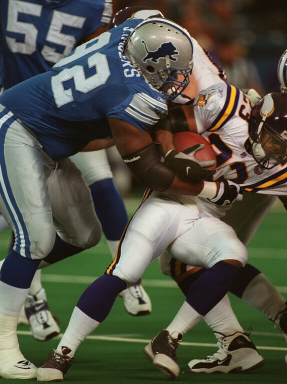 . Detroit Lions defensive tackle Shaun Rogers (left) takes down Minnesota Vikings running back Michael Bennett during the Lions\' 27-24 victory at the Silverdome Sunday.  The Lions are now 1-12.