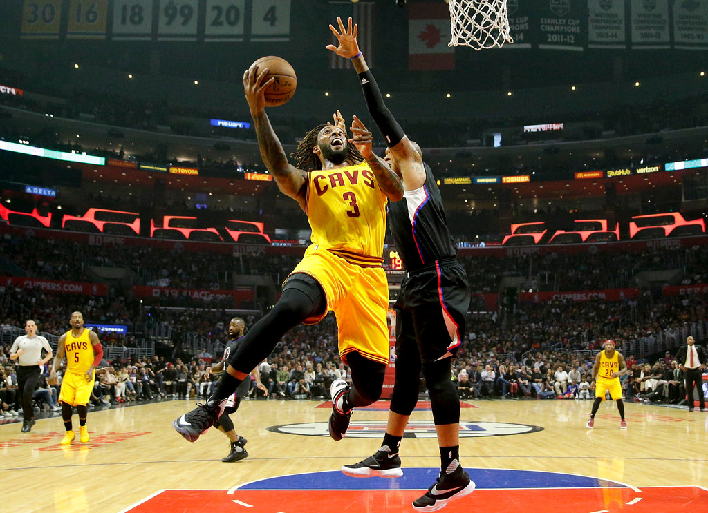 . Cleveland Cavaliers\' Derrick Williams, left, drives to the basket under defense by Los Angeles Clippers\' Marreese Speights during the first half of an NBA basketball game Saturday, March 18, 2017, in Los Angeles. (AP Photo/Jae C. Hong)