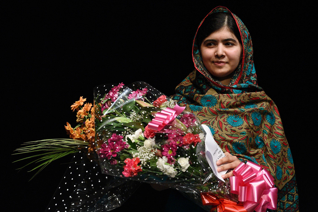 """. Pakistani rights activist Malala Yousafzai holds bouquets of flowers after addressing the media in Birmingham, central England on October 10, 2014. The Nobel Peace Prize went Friday to 17-year-old Pakistani Malala Yousafzai and India\'s Kailash Satyarthi for their work promoting children\'s rights. Seventeen-year-old Nobel Peace Prize winner Malala Yousafzai said she was \""""honoured\"""" to be the first Pakistani and the youngest person to be given the award and dedicated the award to the \""""voiceless\"""". \""""This award is for all those children who are voiceless, whose voices need to be heard,\"""" she said. AFP PHOTO / OLI SCARFF/AFP/Getty Images"""