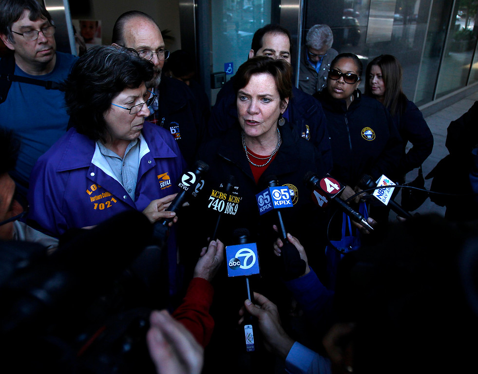 . Josie Mooney, lead negotiator of Service Employees International Union local 1021, center, standing next to Roxanne Sanchez, president of SEIU 1021, left, speaks to the media outside of the Caltrans offices in downtown Oakland, Calif. on Sunday, Aug. 11, 2013.  (Nhat V. Meyer/Bay Area News Group)