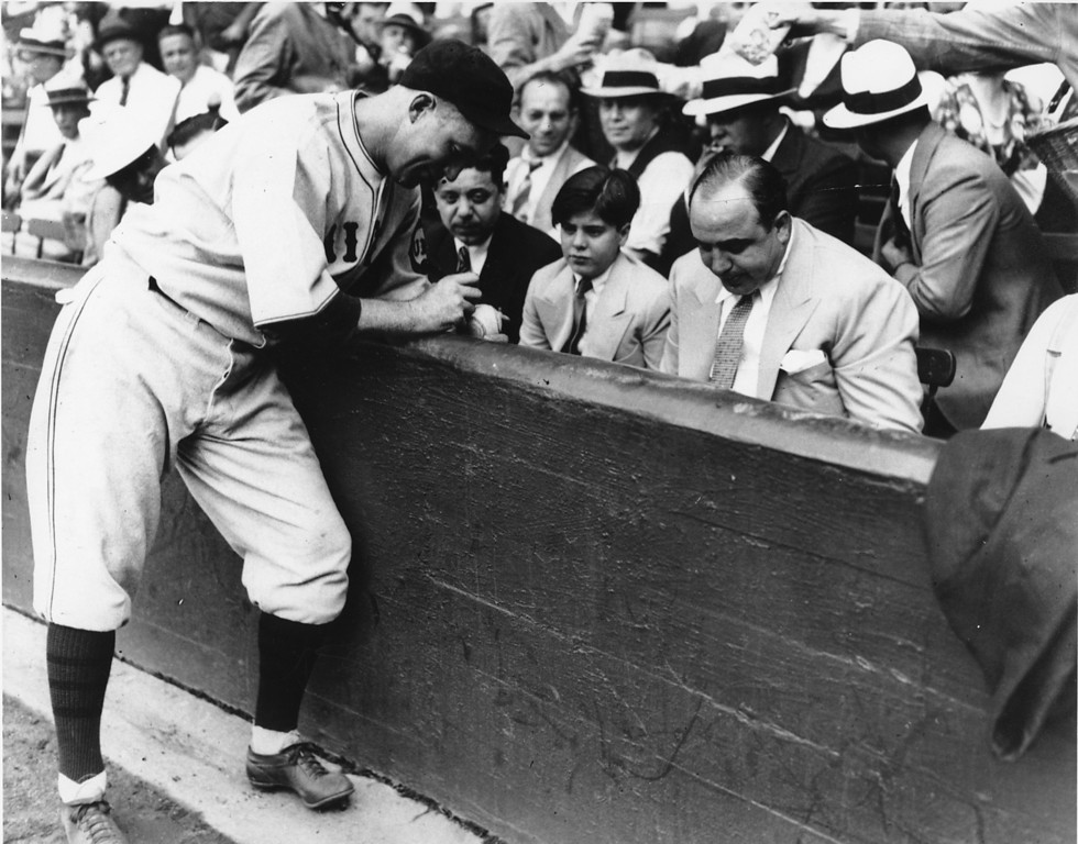 . Surrounded by his watchful lieutenants, Chicago\'s crime boss Al Capone, right, and his 12-year-old son, Al Jr. gets Gabby Harnett of the Cubs to autograph a baseball just before the Cubs defeated the White Sox, 3 to 0 on Sept. 9, 1931.  Note the watchfulness of one of Capone\'s bodyguards behind him, at the ready as a popcorn vendor rubbed against him.  (AP Photo)