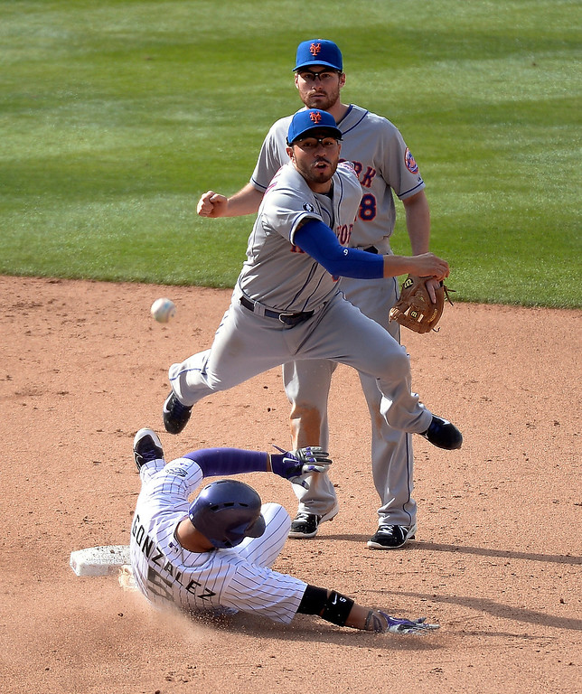 . Colorado Rockies left fielder Carlos Gonzalez (5) gets doubled up by shortstop Omar Quintanilla (0) as he throws to first baseman Lucas Duda to complete the double play in the 8th inning May 4, 2014 at Coors Field. (Photo by John Leyba/The Denver Post)