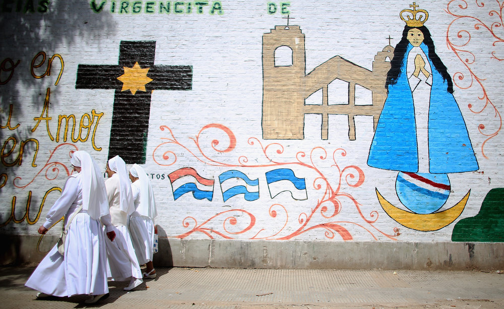 . Nuns walk past a mural near the Virgin of the Miracles of Caacupe church following Sunday Mass in the Villa 21-24 slum, where archbishop Jorge Mario Bergoglio, now Pope Francis, used to perform charity work, on March 17, 2013 in Buenos Aires, Argentina. Francis was the archbishop of Buenos Aires and is the first Pope to hail from South America. Some locals are now affectionately calling Francis, known for his charity work in the slums, the \'slum pope.\'  (Photo by Mario Tama/Getty Images)