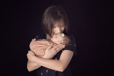 Colour studio photograph of mother kissing top of her newborn baby's head