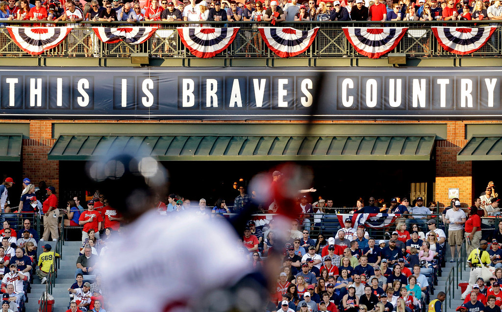 . Fans watch from the outfield as Atlanta Braves\' Jason Heyward swings at a pitch in the first inning of an opening day baseball game against the Philadelphia Phillies, Monday, April 1, 2013, in Atlanta. (AP Photo/David Goldman)