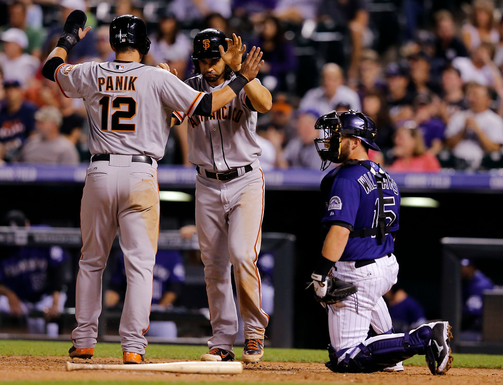 . San Francisco Giants\' Joe Panik (12) and Angel Pagan celebrate scoring on a Buster Posey two RBI double against the Colorado Rockies during the seventh inning of a baseball game Tuesday, Sept. 2, 2014, in Denver. (AP Photo/Jack Dempsey)
