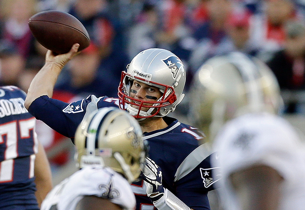 . New England Patriots quarterback Tom Brady, rear, passes over the rush by the New Orleans Saints in the first half of an NFL football game Sunday, Oct.13, 2013, in Foxborough, Mass. (AP Photo/Steven Senne)