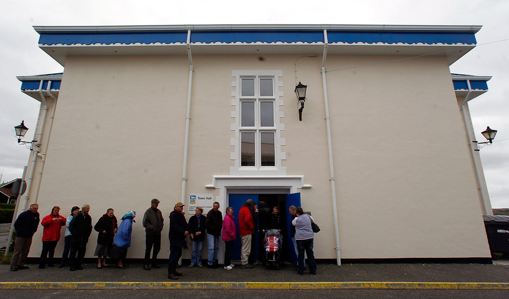 . People line up to cast their vote at the Town Hall polling station in Stanley, March 10, 2013.  Residents of the Falkland Islands started voting on Sunday in a sovereignty referendum that seeks to counter Argentina\'s increasingly assertive claim over the British-ruled territory. REUTERS/Marcos Brindicci