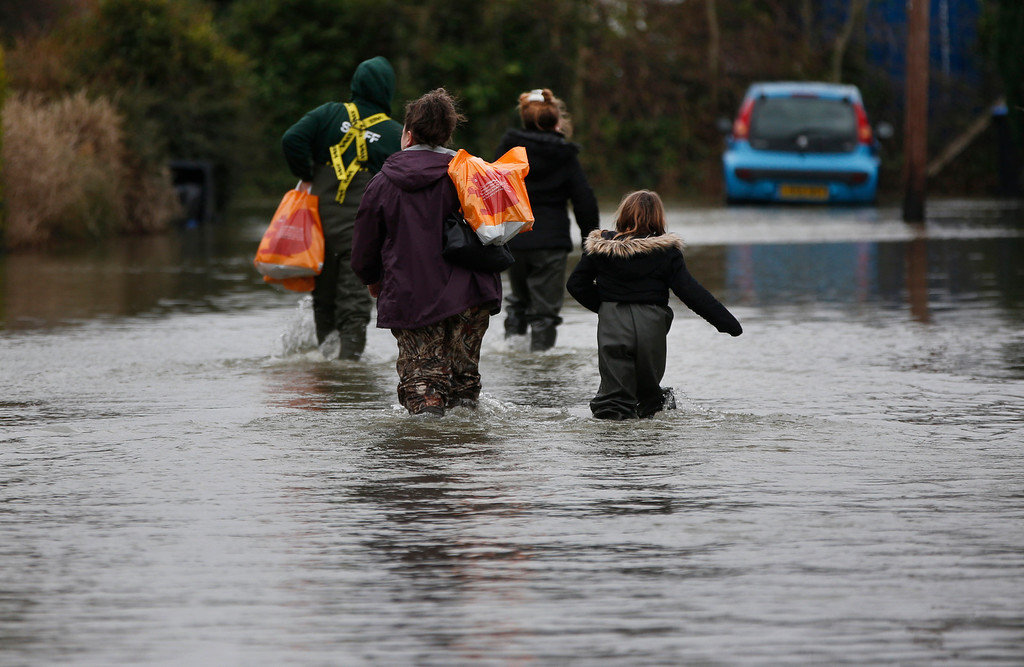". Members of the Bill family, carrying groceries, return to their house through the flooded part of the town of Staines-upon-Thames, England, Wednesday, Feb. 12, 2014. Prime Minister David Cameron insisted Tuesday that money is no object in the battle against the widespread flooding that has engulfed parts of England. Canceling a visit to the Middle East to oversee flood-fighting efforts, he told journalists that ""whatever money is needed for this relief effort will be spent\"" as Britain deals with some of its wettest weather in 250 years. (AP Photo/Lefteris Pitarakis)"