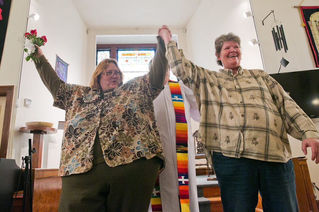 ". Stacy Rutz, left, and Maryann Day, right, hold their arms up after Rev. Bill Freeman announces the couple married during their wedding ceremony at the Harbor Unitarian Universalist church in Muskegon on Saturday, March 22, 2014. Day and Rutz said they\'ve been together for 14 years. ""We\'ve been through a lot, hard times times and good times,\"" Day said during her vows. \""You\'ve helped me raise my children, you\'ve supported me in every decision I\'ve made. I will love you until the day that I close my eyes.\"" (AP Photo/The Chronicle, Natalie Kolb)"