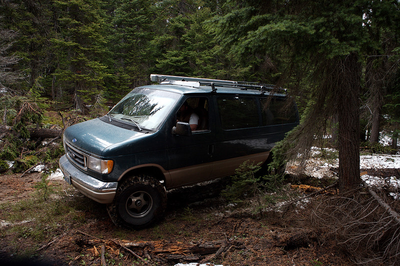 One bad-a** four wheel drive Econoline van, jumping downed trees with ease.