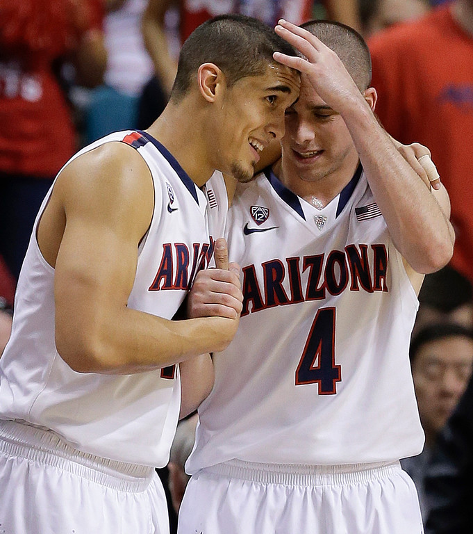 . Arizona\'s Nick Johnson, left, and T.J. McConnell react as they watch play from the bench late in the game against Colorado during the second half of an NCAA college basketball game in the semifinals of the Pac-12 Conference on Friday, March 14, 2014, in Las Vegas. Arizona won 63-43. (AP Photo/Julie Jacobson)