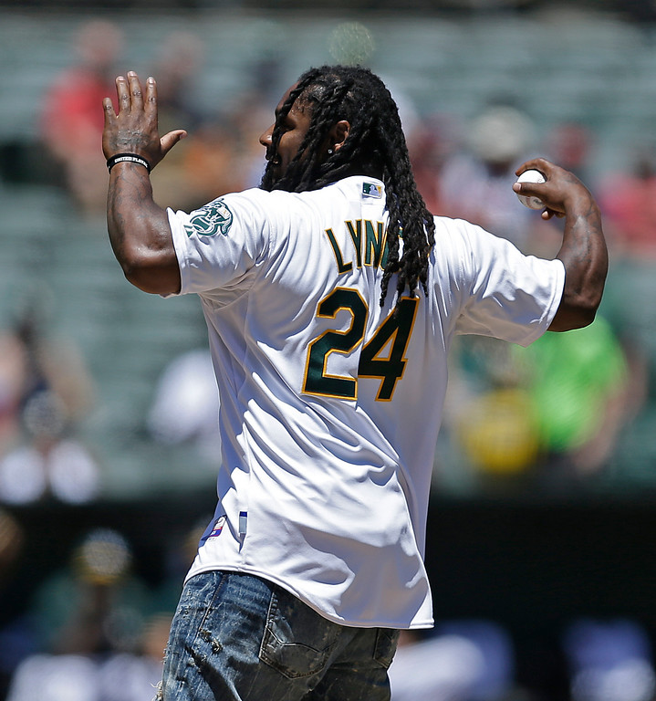 . Oakland Raiders\' running back Marshawn Lynch prepares to throw the ceremonial first pitch prior to a baseball game between the Oakland Athletics and the Cleveland Indians, Sunday, July 16, 2017, in Oakland, Calif. (AP Photo/Ben Margot)
