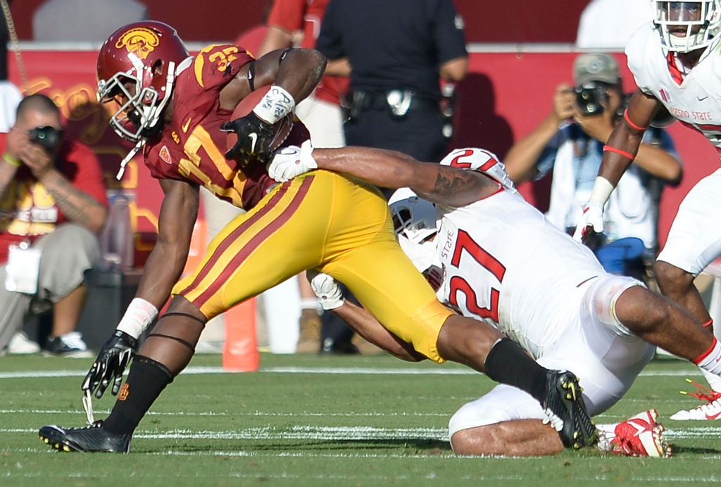 . USC #37 Javorius Allen is brought down by Donavon Lewis in the 2nd quarter. USC played Fresno State at the Los Angeles Memorial Coliseum for the first game of the year. Los Angeles, CA. 8/30/2014(Photo by John McCoy Daily News