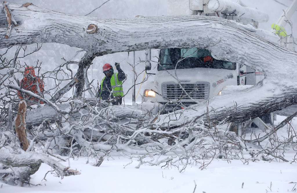 . Workers remove a fallen tree from a road and repair power lines during a winter storm, Tuesday, March 13, 2018, in Norwell, Mass. A nor\'easter that could deliver up to 2 feet of snow to some areas socked New England on Tuesday, bringing blizzard conditions to parts of Massachusetts, covering highways with snow and knocking out power to tens of thousands. (AP Photo/Steven Senne)