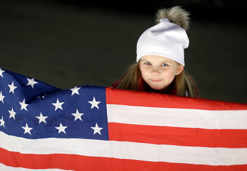 . A young fan with an American flag waits for the start of the men\'s two-man bobsled competition at the 2014 Winter Olympics, Sunday, Feb. 16, 2014, in Krasnaya Polyana, Russia. (AP Photo/Natacha Pisarenko)