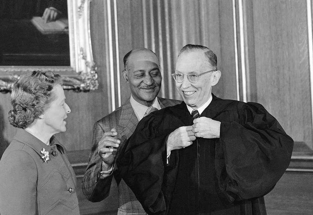 . Lewis F. Powell Jr., 64 years old lawyer from Richmond, Va., puts on a robe before being sworn in Jan. 7, 1972 as an Associate Justice of the Supreme Court. His wife Josephine, is at left. Assisting Powell is Hanford Harrison, robing attendant. (AP Photo)