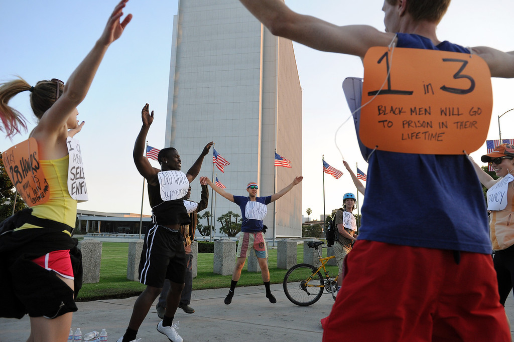 """. Protesters do jumping jacks near the Federal Building before jogging through Westwood on a \""""Smash White Supremacy Fun Run,\"""" Thursday, July 18, 2013. (Michael Owen Baker/L.A. Daily News)"""