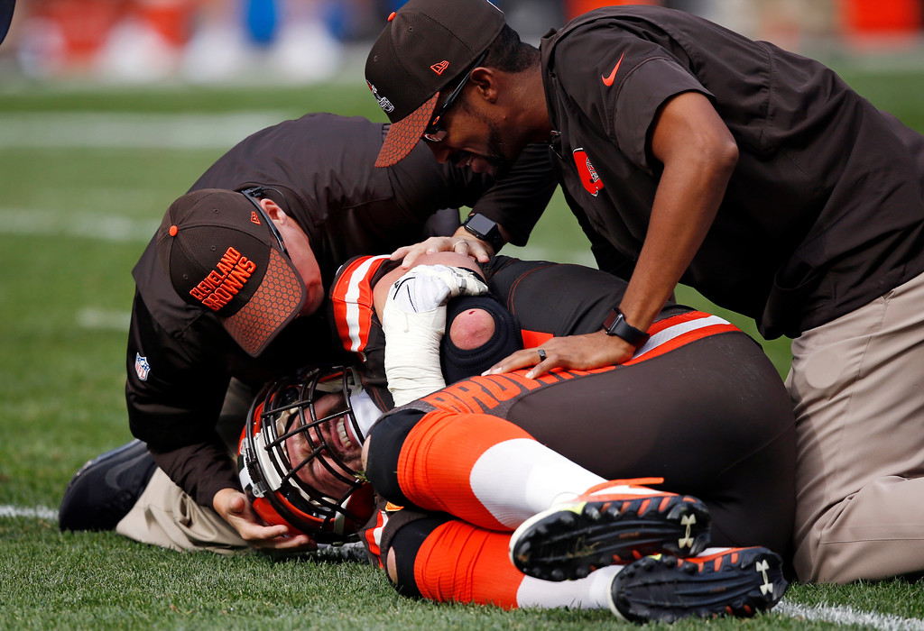 . Trainers, top, check Cleveland Browns tackle Joe Thomas after Thomas was hurt in the second half of an NFL football game against the Tennessee Titans, Sunday, Oct. 22, 2017, in Cleveland. (AP Photo/Ron Schwane)