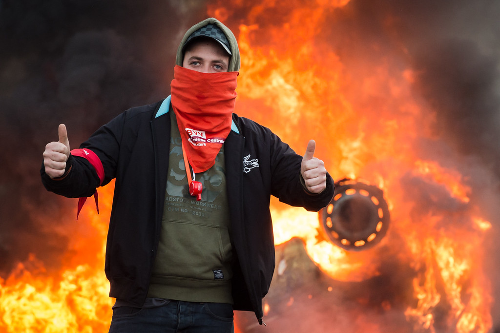 . A protestor gives thumbs up as he stands in front of a burning car during a national trade union demonstration in Brussels, Thursday Nov. 6, 2014. (AP Photo/Geert Vanden Wijngaert)